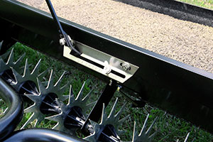 tow-behind aerator-spreader attachment flow control